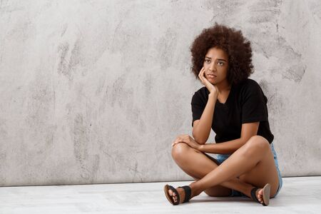 Upset young beautiful african girl sitting over light background. Copy space. Stock Photo