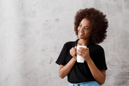 Young beautiful african girl holding cup, smiling over light background. Copy space. Imagens