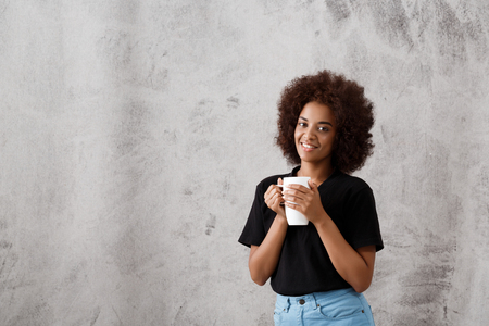Young beautiful african girl holding cup, smiling, looking at camera over light background. Copy space.