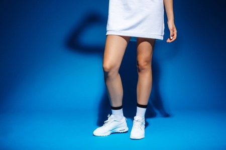 Picture of young fintess girls legs over blue background