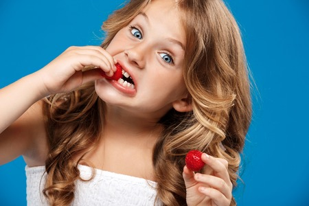 Young pretty girl eating strawberry, looking at camera over blue background. Copy space. Stock Photo