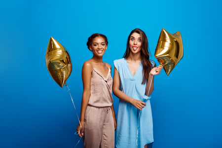 Portrait of two young beautiful girls in dresses looking at camera, holding baloons, smiling, resting at party over blue background. Stock Photo