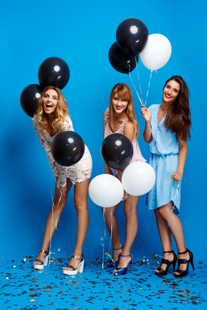 Three young beautiful girls in dresses looking at camera, smiling, holding baloons, resting at party over blue background.
