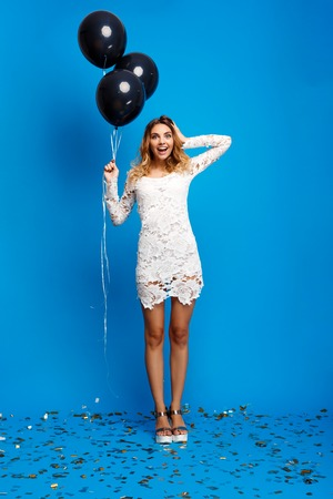 Portrait of young beautiful blonde girl in dress looking at camera, holding baloons, smiling, resting at party over blue background. Stock Photo