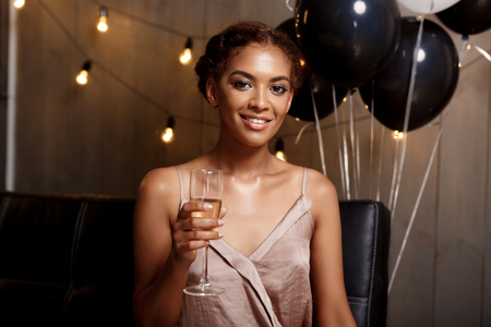 Portrait of young beautiful african girl looking at camera, smiling, holding glass with champagne, resting at party. Stock Photo
