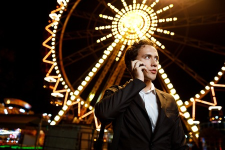 Portrait of young successful businessman over night amusement park. Shallow DOF Stock Photo