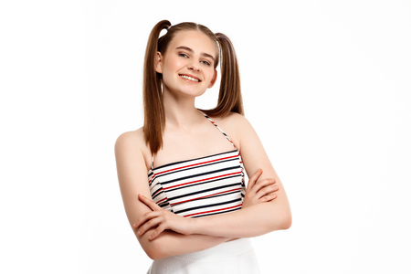 Young girl posing with crossed arms isolated on white background.