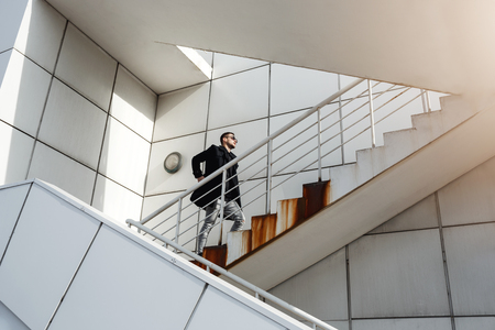 brigt: Stylish man in back coat going upstairs. Minimalizm style. Stock Photo