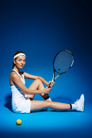 portrait of a female tennis player with racket and ball sitting on floor in studio