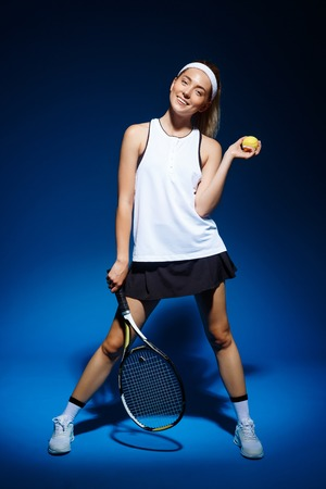 portrait of female tennis player with racket and ball in hand posing in studio