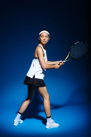 Female tennis player with racket ready to hit a ball.