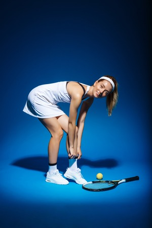 mujer deportista: portrait of female tennis player with racket and ball aside in studio