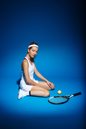Picture of young fintess girl near tennis racket and sitting on floor in studio Stock Photo