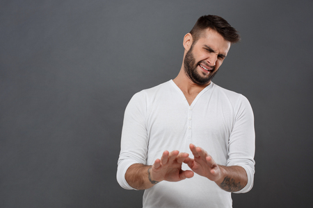 refusing: Displeased man refusing, stretching hands to camera over grey background.