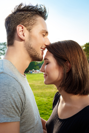 Close up portrait of young beautiful couple smiling, relaxing, kissing in park.