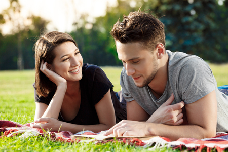 Young beautiful couple smiling, reading, resting on picnic in park.