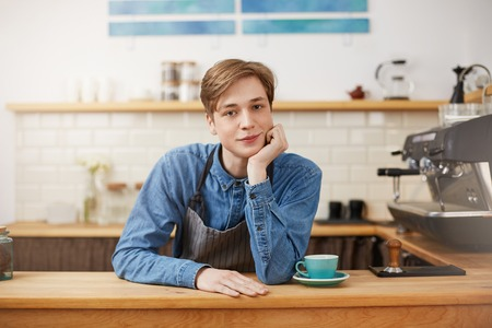 Nice male barista wearing denim shirt and grey striped apron.
