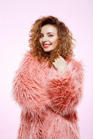 Close up portrait of cheerful smiling beautiful brunette curly girl in pink fur coat over white background.