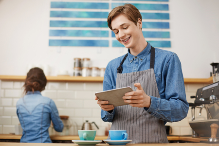 Male cashier taking orders using tab at bright coffee shop.