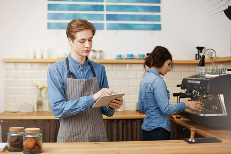 Two cheerful baristas in stylish uniform wroking at bar counter. Stock Photo