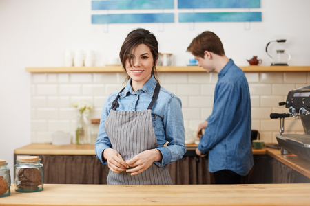 Beautiful female barista in uniform smiling cheerfully taking orders. Stock Photo