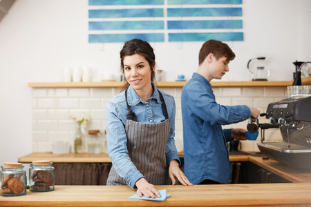 Young nice baristas in uniform working at bar counter.