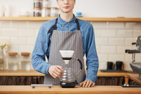 Cropped image of young barista in uniform at bar counter.