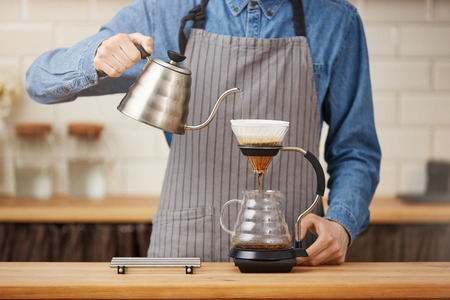 Coffee brewing gadgets. Male bartender brewing pourover coffee at bar.