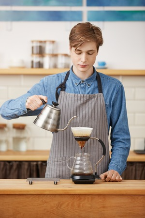 Making pourover coffee. Nice barista preparing coffee drink, looking concentrated.