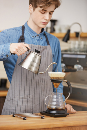 Male barista pouring water through grounds making pourover coffee.