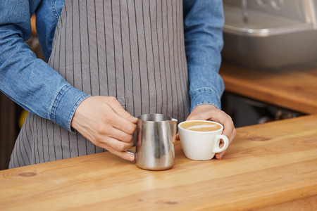 Barista finished latter art, holding white cup and pitcher. Stock Photo