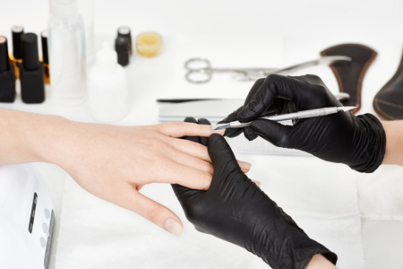 Woman receiving  manicure procedure at nail salon. Beauty care.