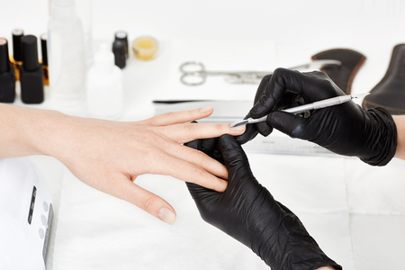 Manicrurist in gloves pushing cuticle on womans ring finger.