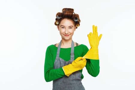 Young white woman wears yeallow rubber gloves and smoles