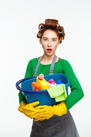 Surprised nice woman holds blue bucket full of cleaning tools Stock Photo