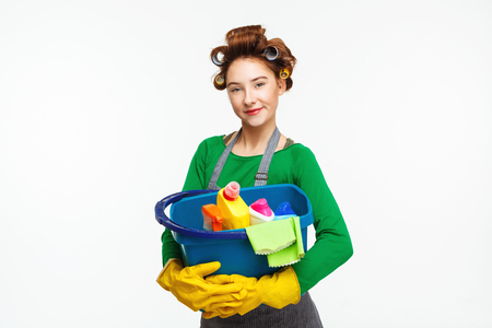 hair roller: Adorable housewife poses holding cleaning tools wearing yellow gloves