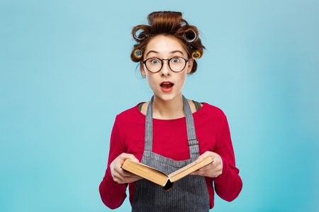 Nice girl wearing glasses and curlers looks surprised while reading