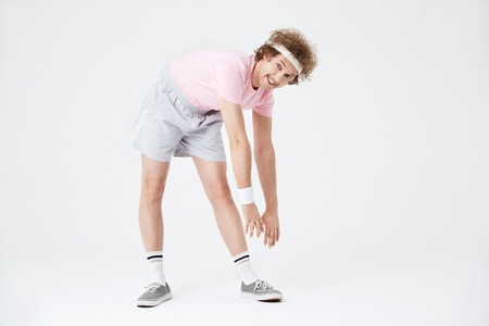 Sporty man stretching back and leg muscles looking straight