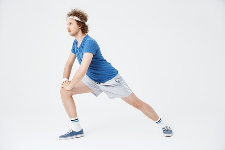 Side view of retro man lunging forward, looking straight Stock Photo