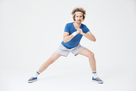 Guy in retro sport suit doing stretching exercises. White background Stock Photo