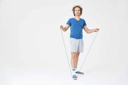 Man in retro sport outfit holding jumping rope in hand