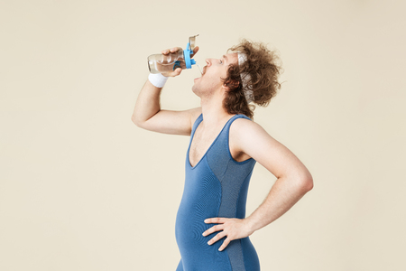 Side shot of thursty man drinking water from glass bottle Stock Photo