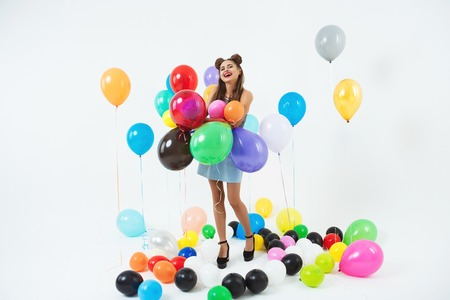 Smiling girl looks happy holding bunch of big balloons