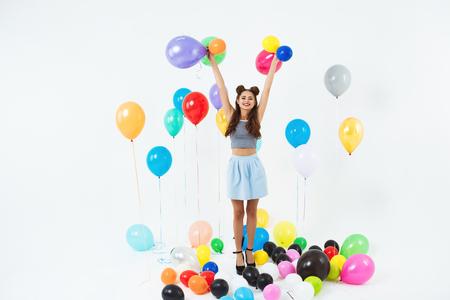 Amazing teen girl looking straight, holding helium ballons on white Stock Photo