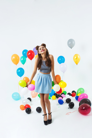 Charming girl in fashion look posing with small balloons