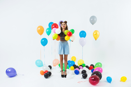 Pretty woman posing with colourful helium balloons after big party Stock Photo