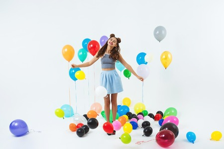 Charming lady in trendy clothing looks happy holding balloon bunch Stock Photo