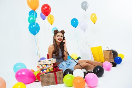 Portrait of funny girl taking phone conversation sitting on floor