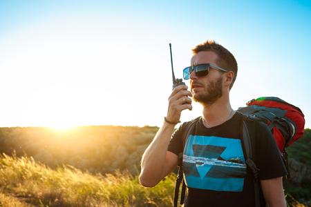 Young handsome man talking on walkie talkie radio, enjoying canyon view. 스톡 콘텐츠