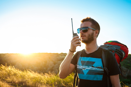 Young handsome man talking on walkie talkie radio, enjoying canyon view. Foto de archivo